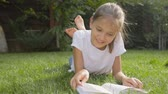 Dolly shot of beautiful girl reading book on grass at park