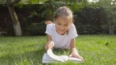 Dolly shot of smiling brunette girl reading book on grass at backyard
