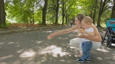 Happy smiling mother with baby son throwing bread to pigeons at park Stock Footage