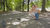 Cute 1 year old baby boy feeding pigeons with mother at park