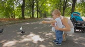Cute baby boy and young mother feeding pigeons at park