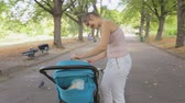 pram : Steadicam shot of young mother giving milk in bottle to her baby son sitting in pram at park
