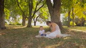 Adorable baby boy playing with his mother on blanket under tree at park