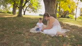 Steadicam shot of happy young woman sitting with her baby son on grass under tree Stock Footage