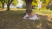 Steadicam shot of happy young mother and baby resting under tree at park Stock Footage