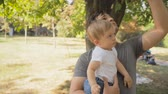 Portrait of happy young father cuddling his baby son at park under tree Stock Footage