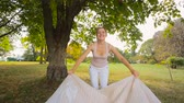 Beautiful smiling woman unwrapping and sitting on blanket under tree at park