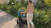 Beautiful young mother walking with baby sitting in pram  on the street Stock Footage