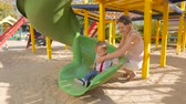 Cute smiling baby boy riding on the slides with mother at playground