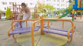 Cute smiling baby boy rotating carousel on playground Stock Footage