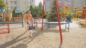 Happy young mother swinging her baby son the playground at sunny day Stock Footage