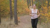 fitness : Tired young woman taking break while jogging at forest