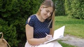 журнал : . Slow motion footage of beautiful young woman sitting in park on grass and writing a diary Стоковые видеозаписи