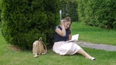 шариковая ручка : Beautiful young woman sitting in park on grass and writing a diary. Slow motion footage