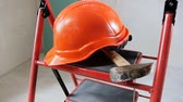 ajustável : Slow motion footage of red hardhat and hammer lying on stapladder