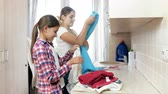 folding machine : 4k footage of beautiful smiling girl helping her mother doing housework in laundry