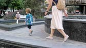 waterworks : Slow motion video of 2 years old toddler boy walking with mother in park