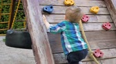 amateur : Slow motion video of toddler boy trying to climb on wooden wall at playground in park Stock Footage