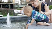 waterworks : Slow motion video of cute toddler boy with mother playing with fountain at park