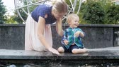waterworks : Slow motion video of cheerful toddler boy splashing and playing with young mother in fountain at park Stock Footage