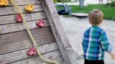 amateur : Slow motion video of adorable toddler boy walking on children playground at park