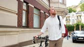 舗装された : 4k footage of handsome hipster man with vintage bicycle walking on street of old town 動画素材