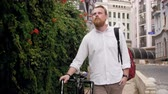 jazda na rowerze : 4k footage of stylish red bearded man with bicycle walking on street