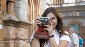 momentka : Slow motion video of happy cheerful tourist girl walking with vintage camera