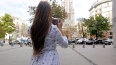 momentka : Slow motion video of young brunette woman making photographs of old cathedral