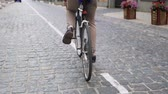 ciclista : Slow motion low angle video of young man sitting on vintage bicycle and riding on paved road