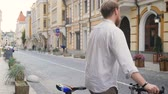 ingázás : Toned slow motion footage of young berded man sitting on bicycle and riding on old street Stock mozgókép