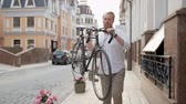 ride to work : Slow motion footage of stylish young man carrying old vintage bicycle on shoulder