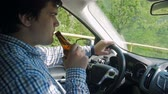 delincuente : Slow motion footage of irresponsible male driver drinking alcohol while driving car Archivo de Video