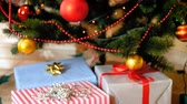 balicí papír : Closeup 4k footage of stack of gift boxes under Christmas tree at living room