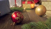 gold coloured : Panning 4k video of colorful baubles and Christmas gifts lying on wooden background