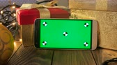 ornamentale : Closeup 4k footage of smartphone leaning on Christmas gift box and glowing light garland. Green chromakey display for inserting your image or video on screen Filmati Stock