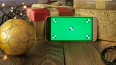 ornamentale : Closeup 4k footage of camera slowly panning over wooden table with Christmas decorations and smartphone. Green chromakey display for inserting your image or video on screen