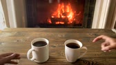 chalet : Closeup 4k footage of couple taking mugs with hot tea from wooden table next tto burning fireplace Stock Footage