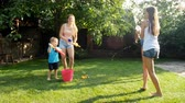 arma curta : 4k video of happy laughing family with children having battle with water guns on hot summer day Vídeos