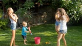 permetezés : 4k video of of happy young family splashing and pouring water over each other at hot sunny day on grass at backyard Stock mozgókép