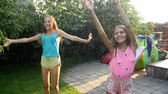 hosepipe : 4k video of two happy laughing teenage girls dancing under water spraying from garden water hose