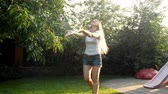 alcançando : 4k video of beautiful young woman dancing under warm rain at summer day on grass at backyard Vídeos