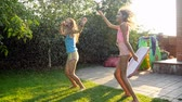 hosepipe : Slow motion footage of two laughing teenage girls dancing and jumping under warm summer rain at backyard