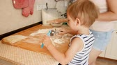 rolling pin : Closeup 4k video of little toddler boy with toy rolling pin helping his mother making pie on kitchen