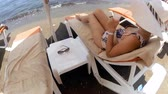 4k video of beautiful young woman in hat relaxing on beach and drinking cocktail