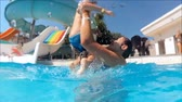 Slow motion footage of happy smiling young mother playing and throwing up her toddler boy in swimming pool at aquapark