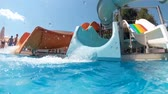 Slow motion footage of three colorful water slides in aquapark at bright sunny day