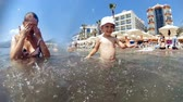SLow motion video of cheerful laughing toddler boy playing with mother and splashing water in the sea Stock mozgókép