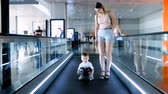 4k video of beautiful smiling young woman with toddler boy standing on travalator at airplane terminal