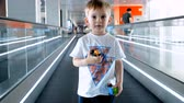 4k video of smiling toddler boy with toys standing on travalator at international airport terminal